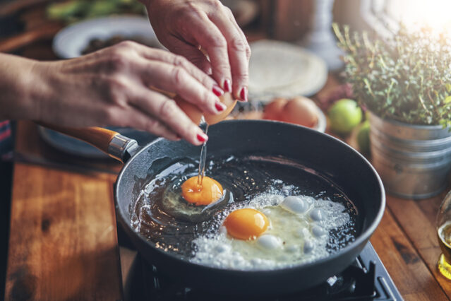 frying an egg hands and pans shot in an article about nutrition myths