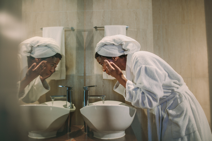 woman doing the oil cleansing method at her bathroom sink