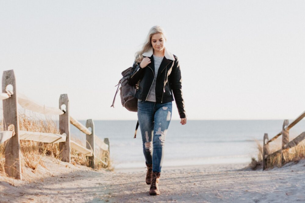 woman carrying a backpack walking on the beach