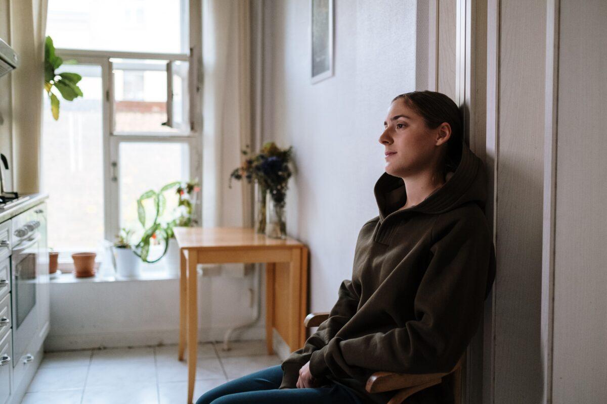 woman sitting in a hallway upset