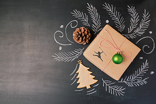 Christmas holiday gift on chalkboard background. View from above