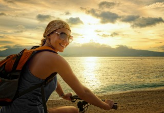 Young woman with backpack standing on the shore near his bike and smiling.