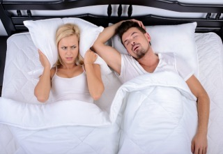 Young woman can not sleep through the snoring of her husband in her bedroom