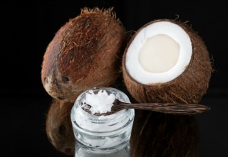 Coconut oil and coconuts on a black background