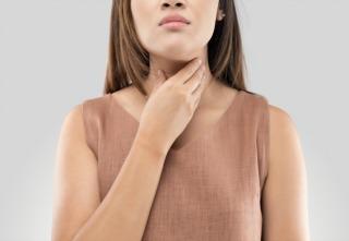 Mulher com dor de garganta no fundo cinza
