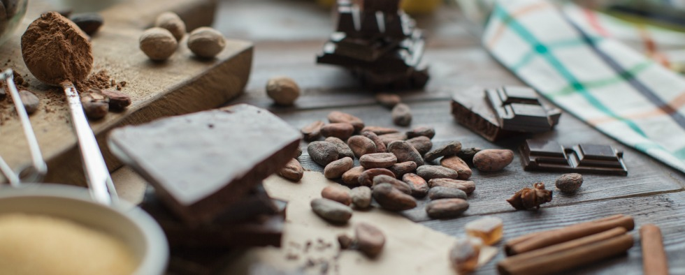 cocoa beans, spices and pieces of chocolate on the wooden table