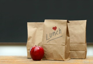 Paper lunch bags with red apple on school desk