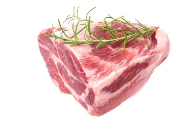 raw chuck steak with rosemary on white background